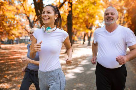 Senior man en vrouw en jonge vrouwelijke instructeur training op frisse lucht. Buitenactiviteiten, gezonde levensstijl, sterke lichamen, fitte figuren. Stijlvolle, moderne sportkleding. Stockfoto