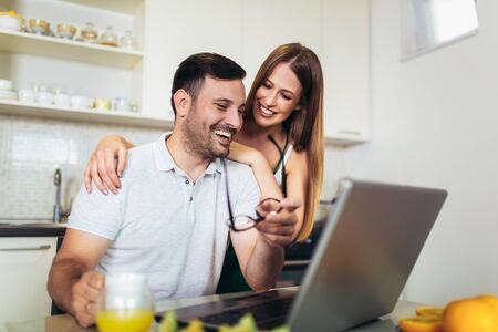 Cute couple using laptop together at home in the kitchen Archivio Fotografico - 129739167