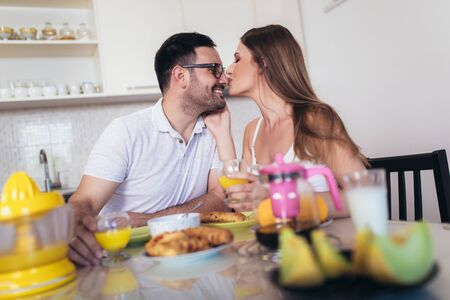 Happy couple enjoying breakfast time together at home. Foto de archivo