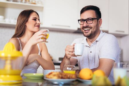 Happy couple enjoying breakfast time together at home.