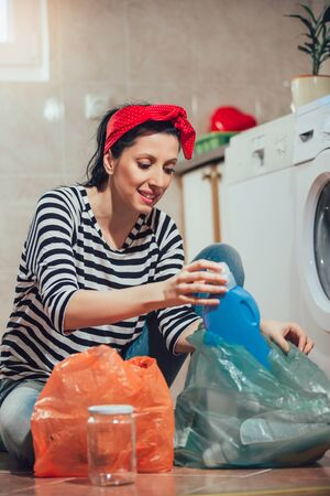 Segregating waste,a daily routine of smiling young woman