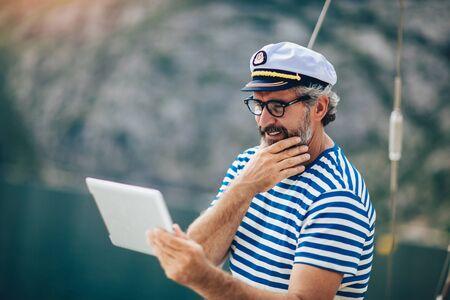 Hombre maduro de pie en la cubierta de su barco y con tableta digital en una tarde soleada.