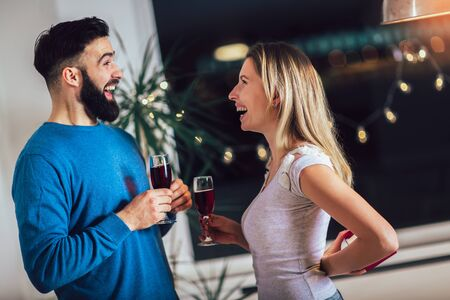 Beautiful happy young couple spending romantic evening together at home, drinking red wine, toasting 写真素材