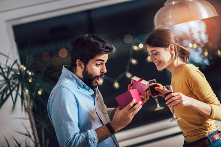 Beautiful young couple is celebrating at home. Pretty girl is giving her boyfriend a gift box Stock fotó
