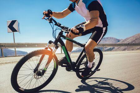 Hombre andar en bicicleta de montaña en la carretera. Concepto de deporte y vida activa. Foto de archivo