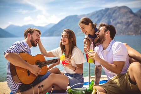 Young people having fun on summer vacation.Happy friends drinking tropical cocktails on the beach. 版權商用圖片 - 129739636