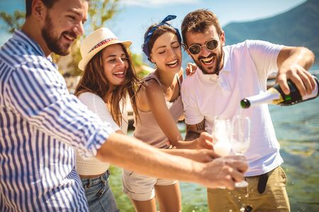 Young attractive and trendy people standing over the sea and drinking champagne while smiling broadly. 版權商用圖片 - 129739715