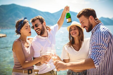 Young attractive and trendy people standing over the sea and drinking champagne while smiling broadly. Stock Photo