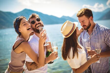 Young attractive and trendy people standing over the sea and drinking champagne while smiling broadly. 版權商用圖片