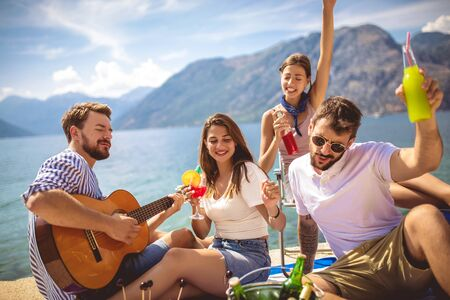 Young people having fun on summer vacation.Happy friends drinking tropical cocktails on the beach. 版權商用圖片 - 129747521