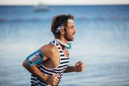 Hombre corriente trotar en la playa. Entrenamiento de corredor masculino fuera de hacer ejercicio. Foto de archivo