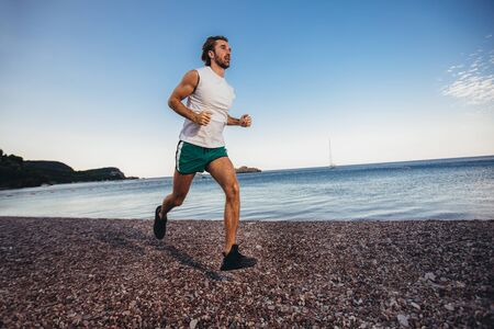 Running man jogging on beach. Male runner training outside working out.