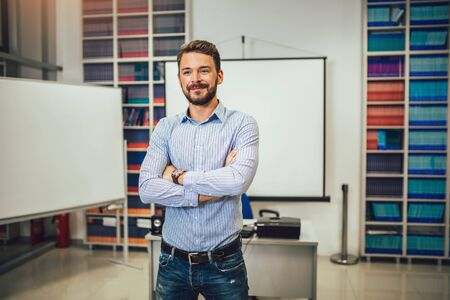 Smiling male coach giving presentation for audience in lecture hall