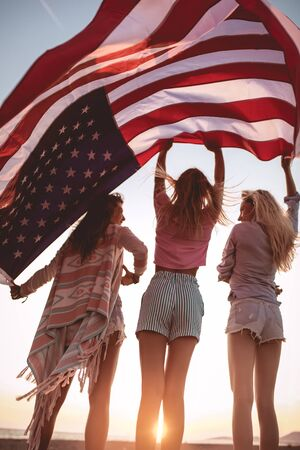 Young friends carrying american flag on the beach Stock fotó
