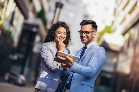 Hombre guapo y mujer hermosa como socios comerciales con tableta digital al aire libre
