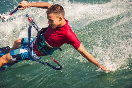 Professional kiter makes the difficult trick on a beautiful background. Kitesurfing Kiteboarding action photos man among waves quickly goes