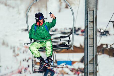 Skier wearing skis, helmet and mask sitting in ski lift cabin taking a selfie Фото со стока