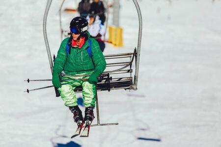 Skier wearing skis, helmet and mask sitting in ski lift cabin Фото со стока