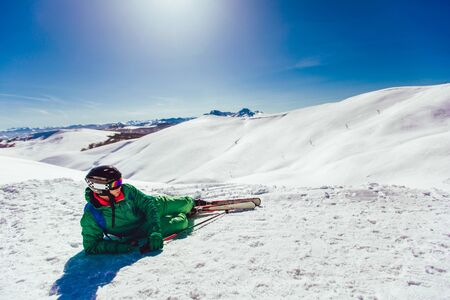 Skier lying on a ski slope at a sunny day and looking somewhere