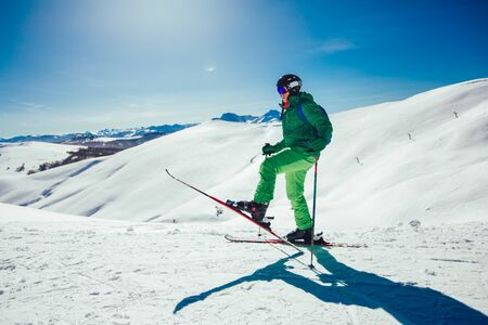 Skier standing with one raised leg on a ski slope at a sunny day and looking somewhere