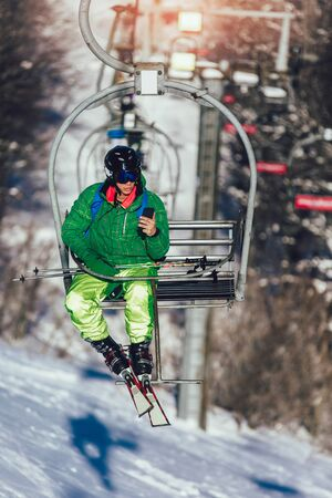 Skier wearing skis, helmet and mask sitting in ski lift cabin holding phone. Фото со стока