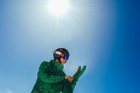 Professional skier in a helmet with a ski mask standing on a glacier is preparing to jump wearing membrane gloves.
