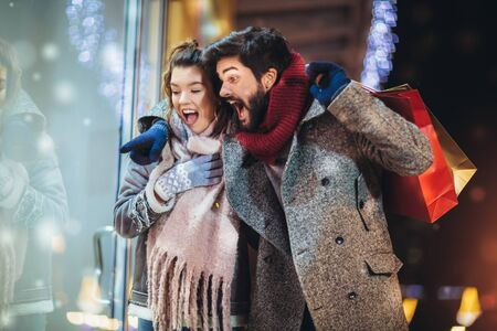 Couple with gift bag on Christmas lights background during walking in the city at evening 스톡 콘텐츠 - 130114001