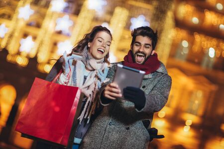 Young couple in the city centre with holidays brights in background. Couple browsing digital tablet. They are using credit card for online shopping.