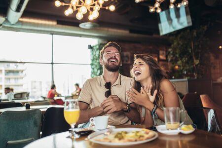 Aufnahme eines jungen glücklichen Paares, das Pizza in einem Restaurant isst und Spaß hat. Standard-Bild