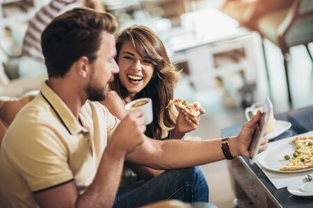 Shot of a young happy couple eating pizza in a restaurant Foto de archivo