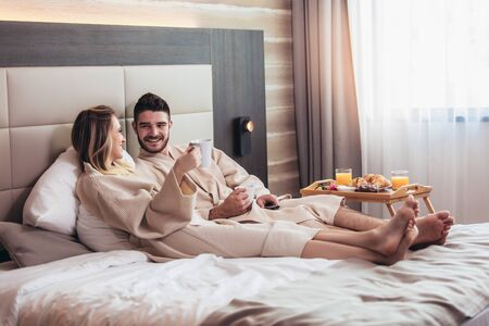 Young happy couple having breakfast in luxury hotel room, watching TV. Stockfoto