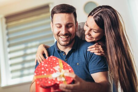 Smiling woman surprises his boyfriend with present at home 免版税图像