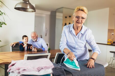 Grandma's ironing clothes, and grandfather plays with his grandson at home. Archivio Fotografico