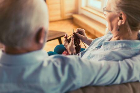 Senior woman teaching her husband the art of knitting woollen clothes. Stockfoto - 130636615