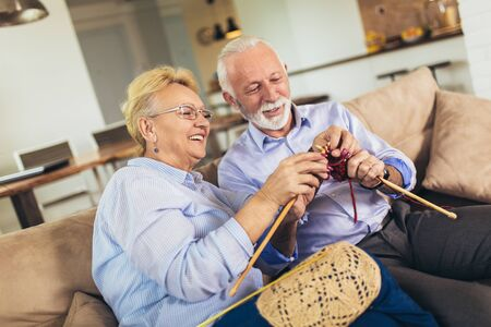 Senior woman teaching her husband the art of knitting woollen clothes.