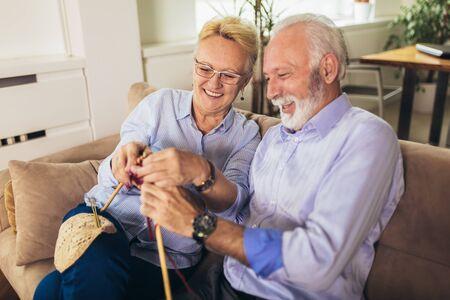 Senior woman teaching her husband the art of knitting woollen clothes.