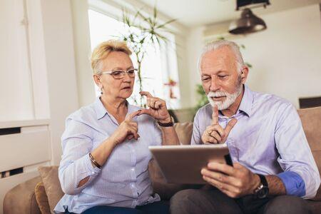 Smiling deaf senior couple talking using sign language on the digital tablets cam