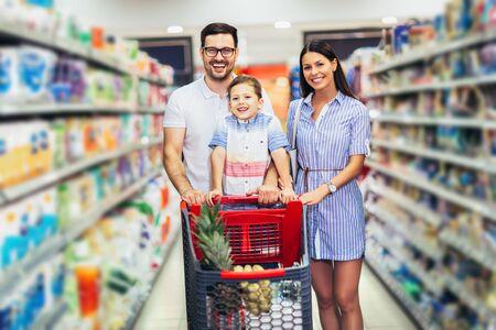 Famille heureuse avec enfant et caddie achetant de la nourriture à l'épicerie ou au supermarché Banque d'images