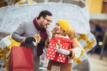 Young couple dressed in winter clothing holding gift boxes outdoor. They eat pretzels.Selective focus.