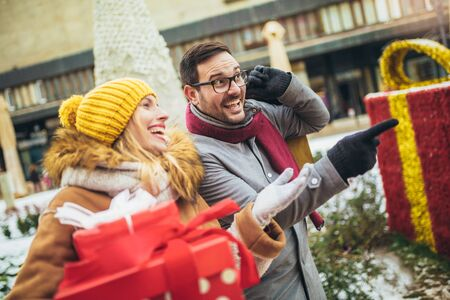 Young couple dressed in winter clothing holding gift boxes outdoor. Selective focus.
