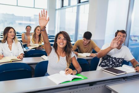 Group of students raising hands in class on lecture Imagens