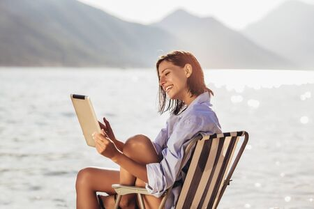 Smiling woman sitting on deck chair by the sea using tablet on a sunny day Imagens