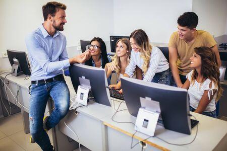 Estudiantes universitarios sentados en un aula, usando computadoras durante la clase. Foto de archivo