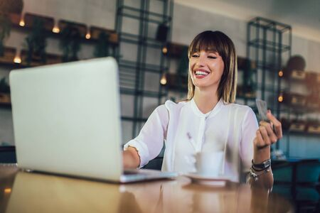 Busy woman using credit card for shopping and paying bills on line while sitting in coffee shop
