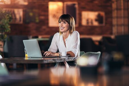 Portrait of a young beautiful businesswoman enjoying coffee during work on portable laptop computer Imagens