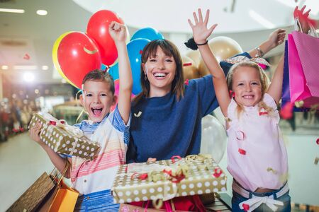 Young mother with children having fun in shopping mall. Imagens