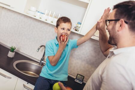 Happy father and kid standing in kitchen in embrace. They holding fruit in hands Stockfoto