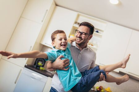 Image of satisfied smiling man piggybacking his son while having fun in modern studio apartment Stockfoto