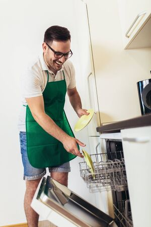 Man does housework in the kitchen, loads the dishes in the dishwashe