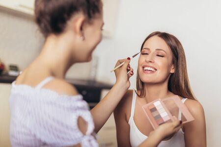 Two smiling girls applying make up at home Imagens